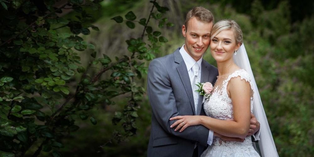 Novomanželé v objetí u zelených keřů.