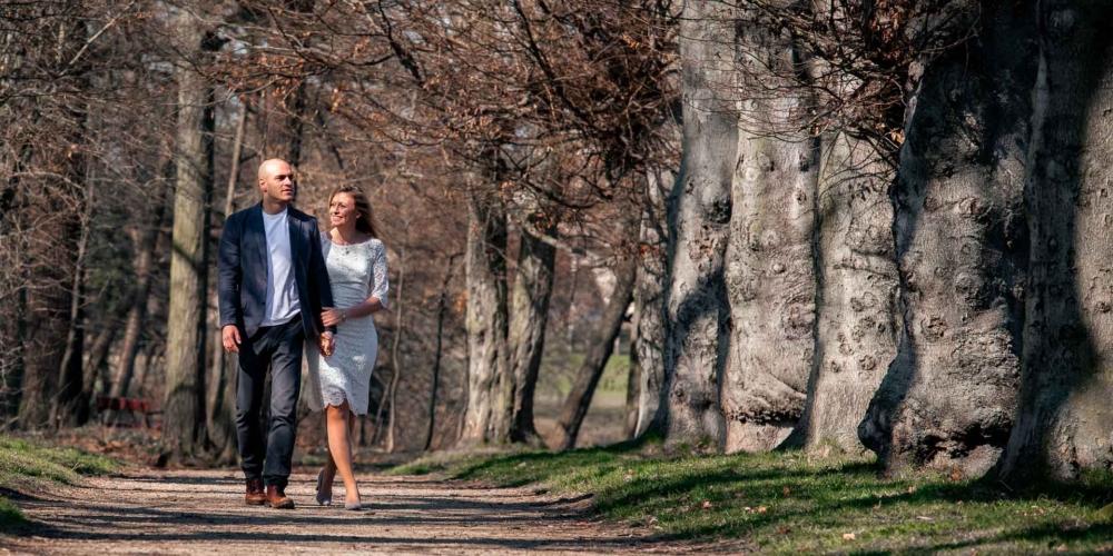 Snoubenci na procházce v parku.