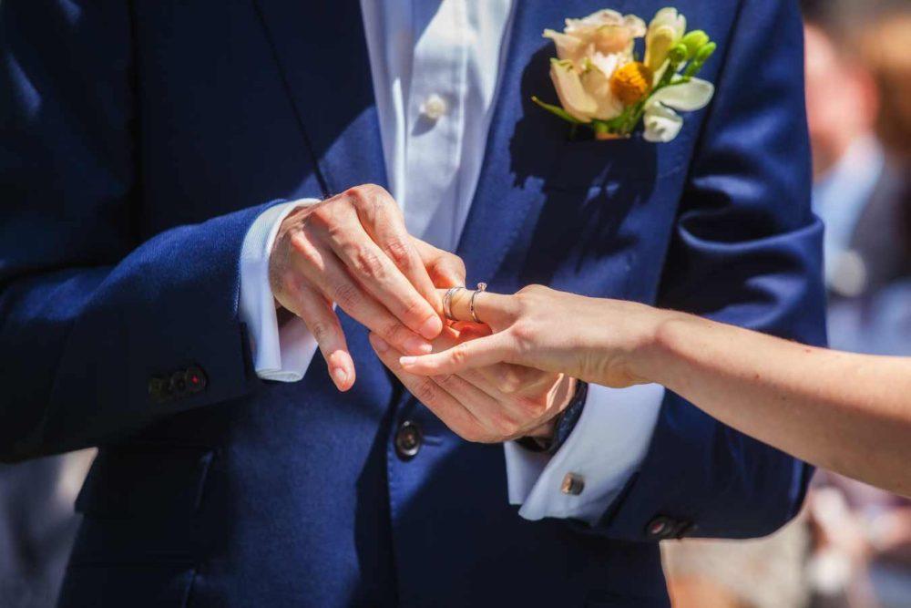 Ženich nasazuje prstýnek nevěstě.