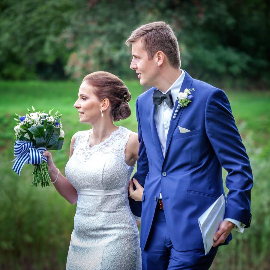 Ženich a nevěsta s kytkou v ruce.