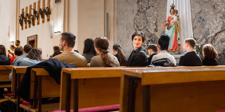 Sedící paní v kostele se dívá dozadu.