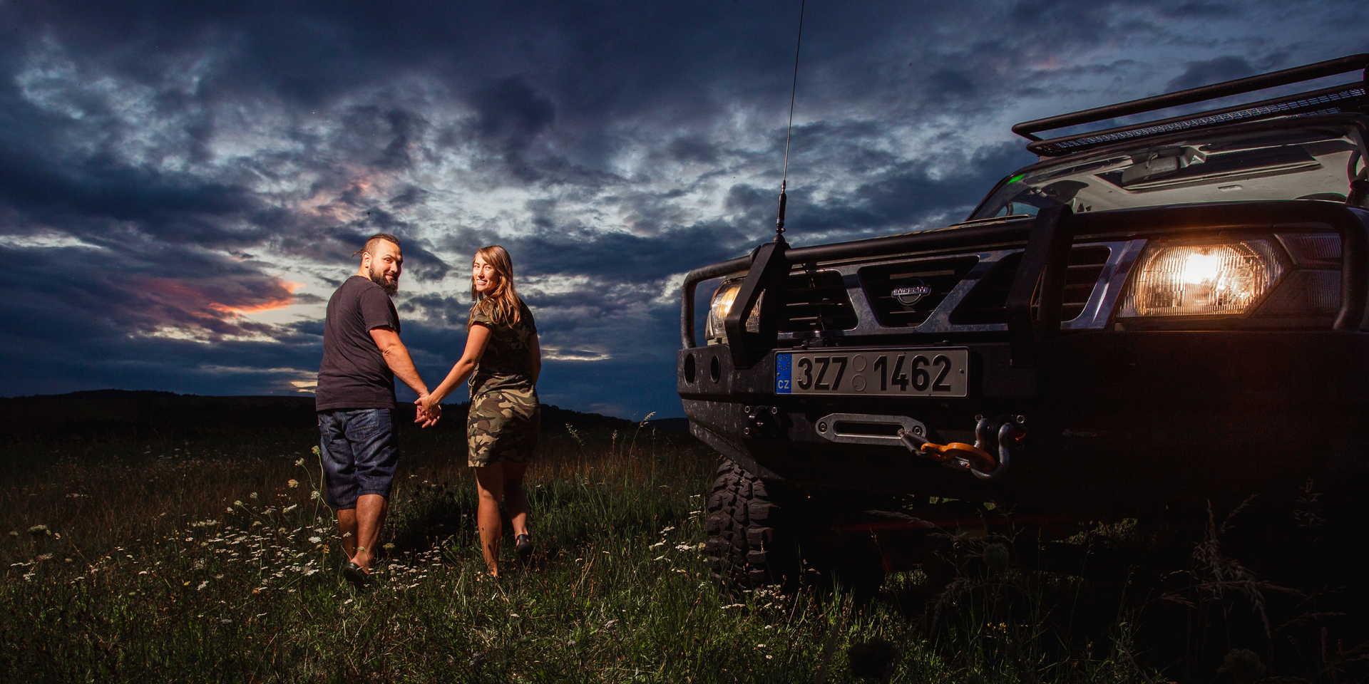 Snoubenci se drží za ruce u vozidla.